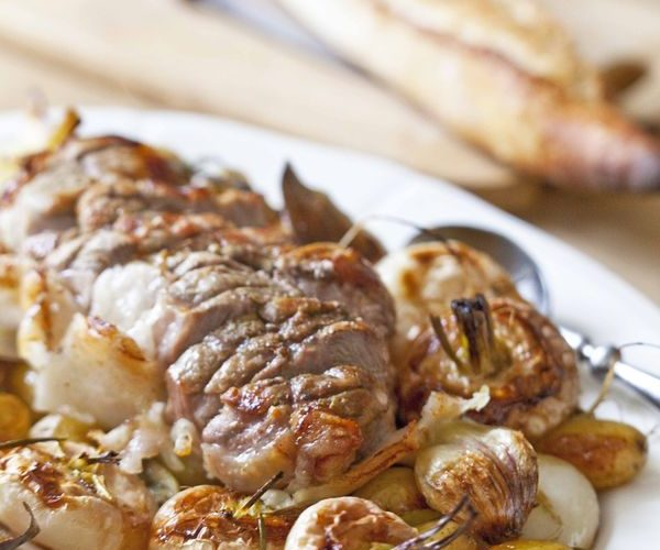 Rôti de porc au four entouré de navets et de pommes confites à l'ail
