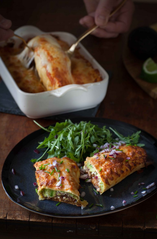 enchiladas coupées en deux et en plat à gratin avec le fromage filant et le tout parsemé d'oignons rouges et de ciboulette ciselés
