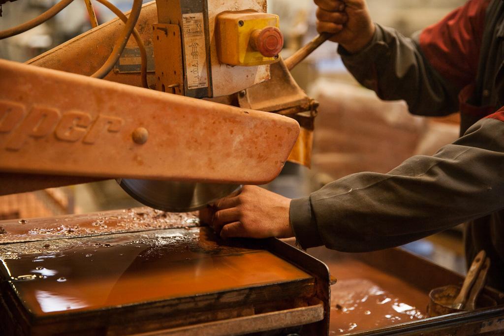 un ouvrier découpe les brques réfractaires une à une pour le montage de la voûte du four Grand-Mère