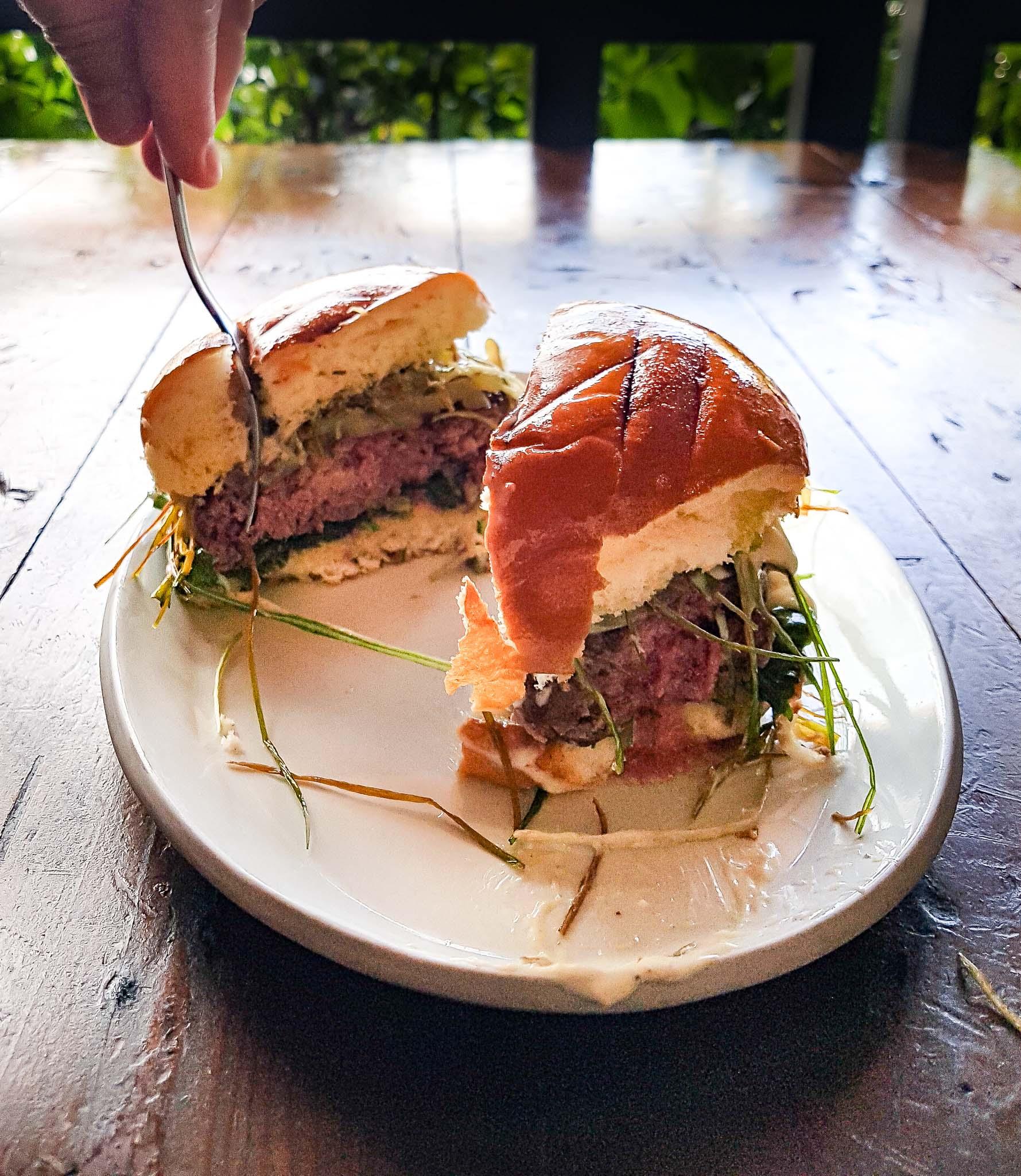 Burger entamé main et assiette blanche Los Angeles autrement