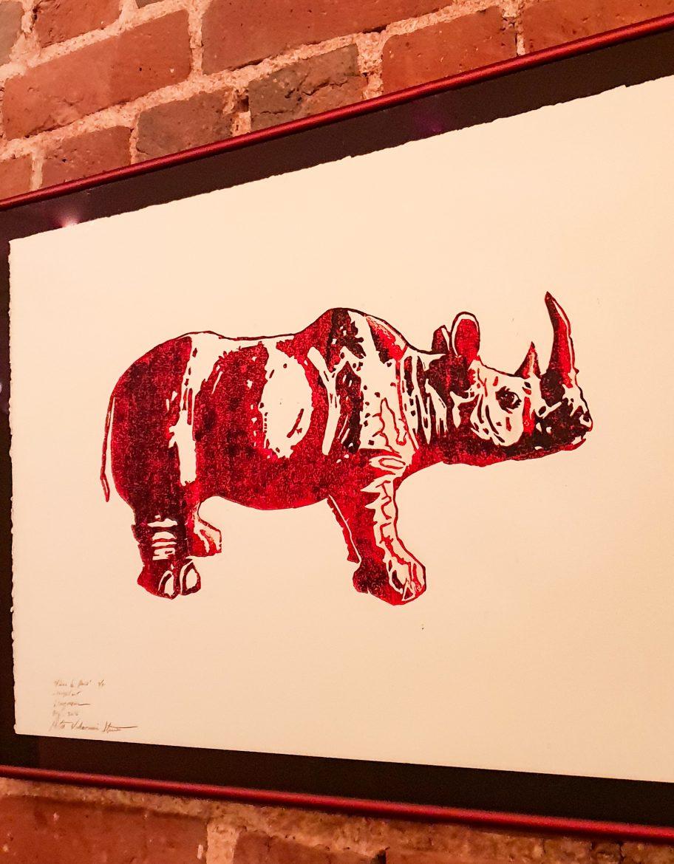Restaurant Rhino Rouge, tableau à l'encre rouge représentant un rhinocéros rouge