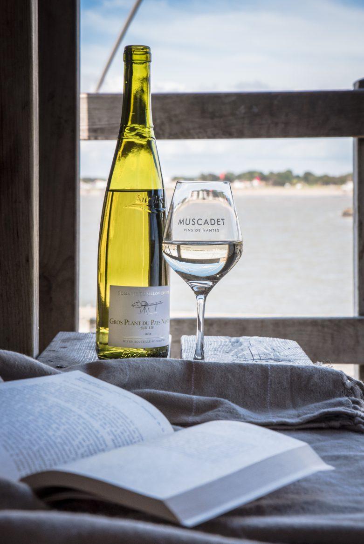 Bouteille de vin blanc de Gros-Plant et verre de vin, devant l'océan et livre ouvert