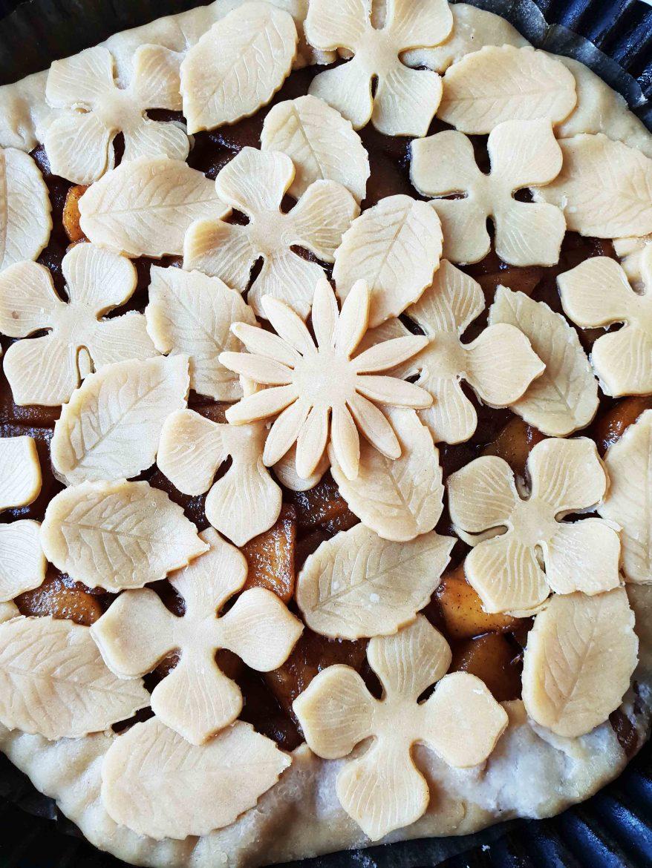 Décorations de pâte crue sur une tarte aux pommes, motif central de fleur