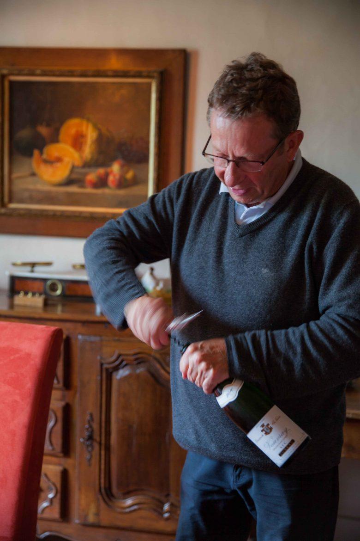 Philippe Foreau, vigneron du Clos Naudin, en train d'ouvrir une bouteille de son Vouvray sec.