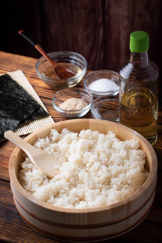 L'étape d'assaisonnement du riz japonais dans un hangari, bac en bois et sa spatule