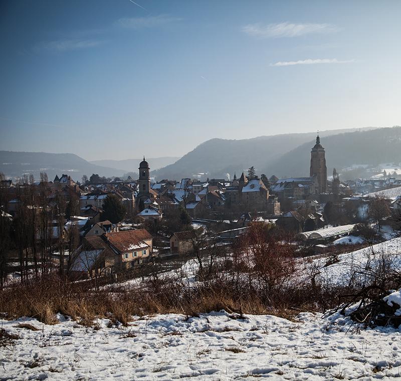 Le village d'arbois sous la neige avec la Cure de la Paroisse à gauche et l'Eglise Saint Just à droite