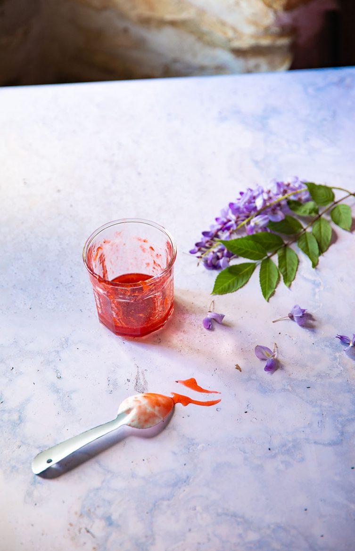 Pot de confiture de fraises vide pour la recette de la génoise aux fraises et à la chantilly, cuillère et trace de confiture sur le marbre d'une table