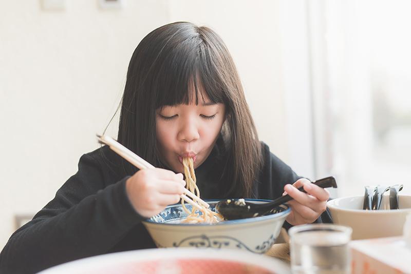 Jeune fille mangeant des ramen